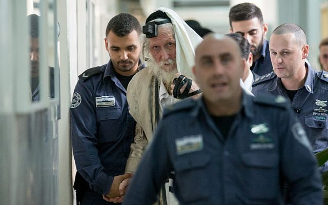 Eliezer Berland covers himself with his tallit (prayer shawl) at the Magistrate Court in Jerusalem, as he is put on trial for sexual assault charges, on November 17, 2016. (Yonatan Sindel/ Flash90)