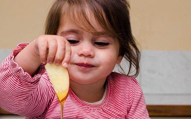 Illustrative. Girl dips apple in honey. (iStock)