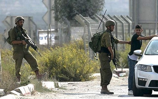 Israeli soldiers search Palestinian man at the Hawara checkpoint south of the West Bank city of Nablus on October 11, 2018, after a stabbing attack nearby. (Jaafar Ashtiyeh/AFP)