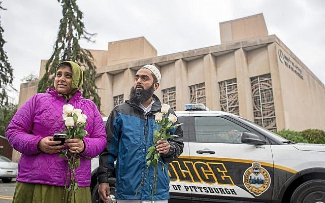 Samina Mohamedali, left, and her husband Kutub Ganiwalla, members of the Dawoodi Bohra Muslim community, both of North Hills, prepare to place flowers on a memorial in front of the Tree of Life Congregation, Sunday, Oct. 28, 2018, in Squirrel Hill neighborhood of Pittsburgh. (Alexandra Wimley/Pittsburgh Post-Gazette via AP via Jewish News)