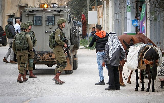 IDF soldiers search for Abed al-Karim Assi, suspected of stabbing an Israeli man to death, in the village of Kifl Haris in the northern West Bank, February 5, 2018. (Nasser Ishtayeh/Flash90)