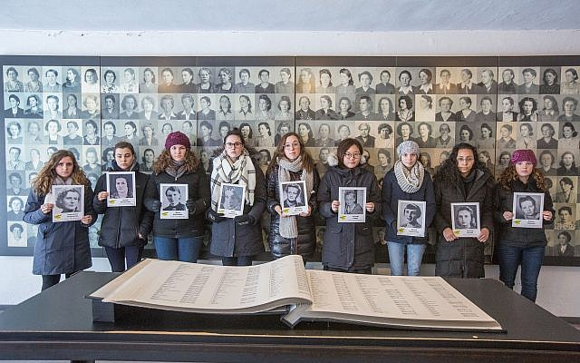 TRTN Fellows hold photographs of Holocaust victims at the Ravensbruck Concentration Camp in Germany.