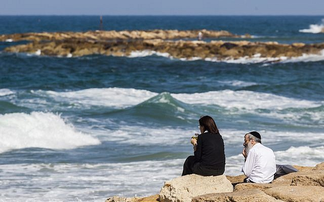 Illustrative: Couple sits on rocks by the sea in Tel Aviv (iStock)