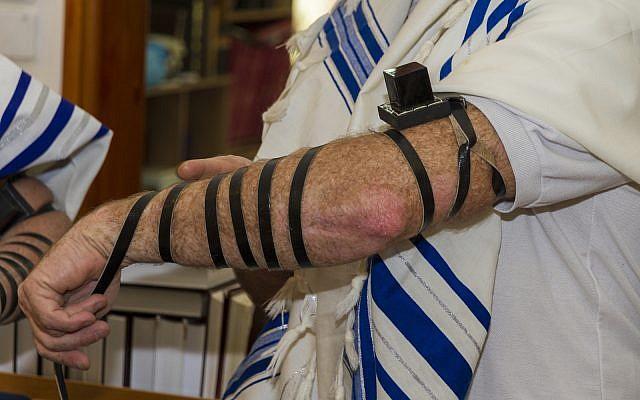 Illustrative: An adult man putting Tefillin on his arm (iStock)
