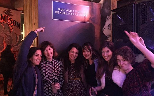 'Layla Tov' activists under a sign at the Kuli Alma Bar signaling a no tolerance policy for sexual harassment (Courtesy of 'Layla Tov').