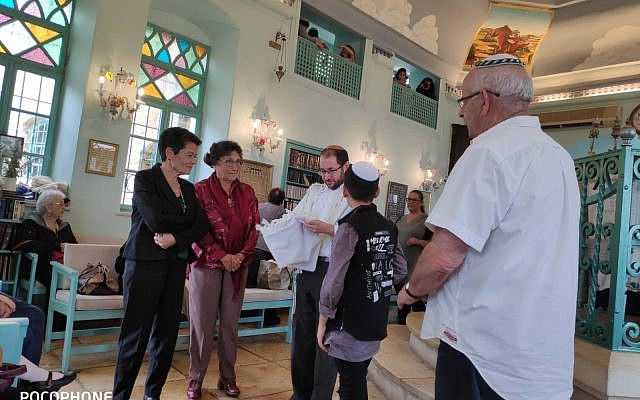 A young Israeli receives a talit from his grandmothers upon becoming a Bar Mitzvah.