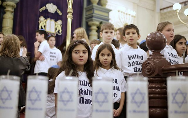 Children from the Park East Day School watch as 11 memorial candles, representing the victims of the Pittsburgh shooting, are placed in front of the synagogue during an inter-faith service in New York, Wednesday, Oct. 31, 2018. (AP Photo/Seth Wenig)
