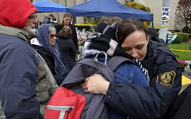 Pittsburgh Police officer Sarah Pratt gets a hug before a Shabbat morning worship service held outside the Tree of Life Synagogue Saturday, Nov. 3, 2018 in Pittsburgh. (AP Photo/Gene J. Puskar)