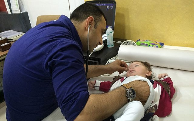 Dr. Ibrahim Abu Zahirah examines a baby with a congenital heart defect in his clinic in Hebron