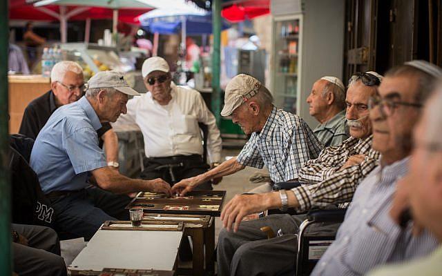 Elderly Israeli men play Backgammon at a coffee shop in the Mahane Yehuda Market in Jerusalem, on May 14, 2017. (Flash90/Hadas Parush)