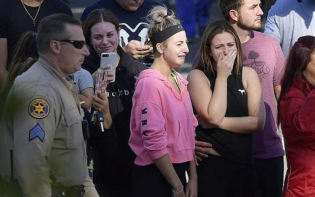 People cry as a law enforcement motorcade escorts the body of Ventura County Sheriff's Department Sgt. Ron Helus from the Los Robles Regional Medical Center, November 8, 2018, in Thousand Oaks, California, after a gunman opened fire Wednesday evening inside a country music bar, killing multiple people including Helus. (AP Photo/Mark J. Terrill)