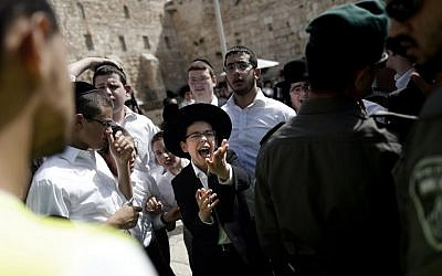Illustrative: A group of Jewish ultra-Orthodox men and boys oppose the prayer service of the Women of the Wall, April 24, 2016. (AFP Photo/Thoman Coex)