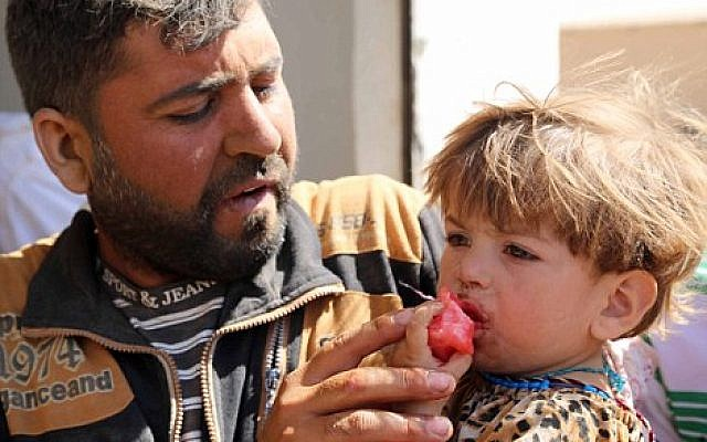 A peshmerga gives much-needed food to a Yazidi child (Getty Images)