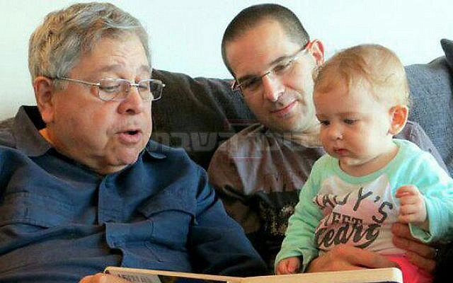Richard Lakin (left) reads a book for his granddaughter, and his son Micha Avni sits next to him, January 2014. (Courtesy, via The Times of Israel)