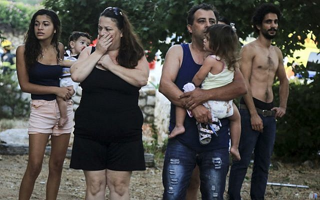 Illustrative: Residents look on in shock after a rocket  hit a house in coastal Ashkelon early on the morning of August 26, 2014. The family living in the house were not injured -- they were on the way to the bomb shelter when the rocket hit. Passersby were hurt by broken glass, while many others suffered from shock. (Edi Israel/Flash90)