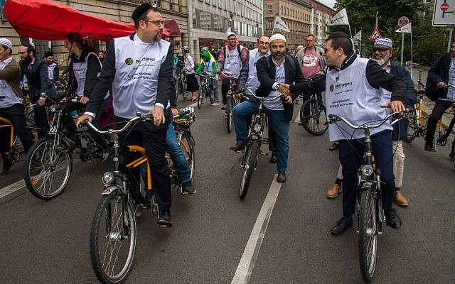 """Jews and Muslims, one person of each faith sharing a tandem bicycle, at the """"meet2respect"""" bicycle demonstration in Berlin on June 24, 2018. (AFP Photo/John MacDougall)"""