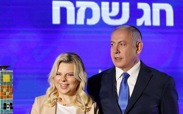 Prime Minister Benjamin Netanyahu stands by his wife Sara before lighting a menorah during the start of Hanukkah in Ramat Gan on December 2, 2018. (GUEZ / AFP)