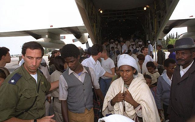 An IDF officer helps Ethiopian immigrants out of a Hercules jet during 'Operation Solomon', May 25, 1991 (Tsvika Israeli / GPO)