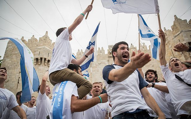 Jewish revelers wave Israeli flags as they celebrate Jerusalem Day by dancing through Damascus Gate on their way to the Western Wall. May 13, 2018. (Yonatan Sindel/Flash90)