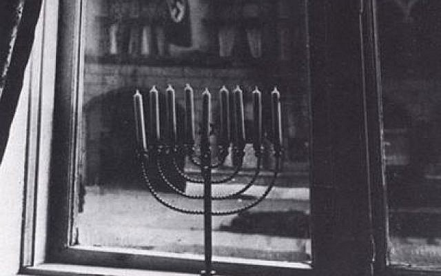 "Taken by Rachel Posner, wife of Rabbi Akiva Posner, in Kiel, Germany. On the back is written, ""Chanukah 5692 (1932) 'Death to Judah.' So the flag says. 'Judah will live forever.' So the light answers."" (Source: Yad Vashem)"