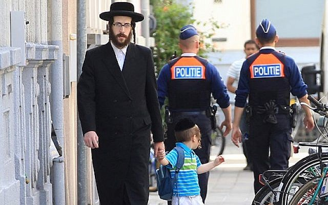 An orthodox Jew and a boy pass two police officers in Antwerp, Belgium, on Sunday, May 25, 2014.   (AP Photo/Yves Logghe via Jewish news )