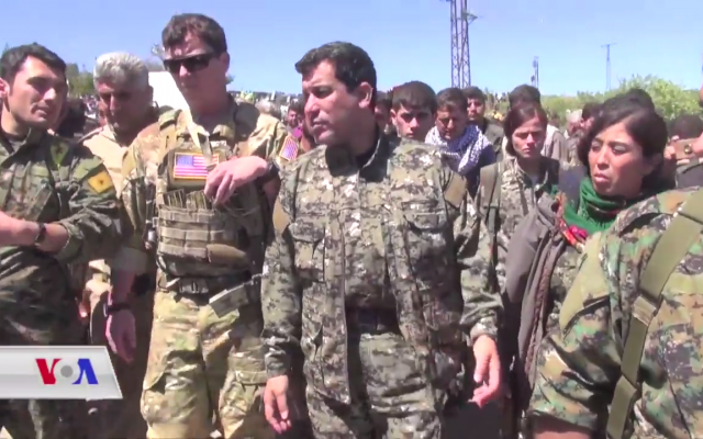An unidentified US military officer accompanies YPG and YPJ officers visiting a town in the northeastern Hasaka Governorate during the aftermath of Turkish airstrikes in the area. (Wikipedia)