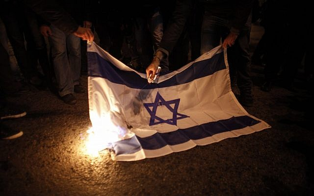 Illustrative: Protesters burn an Israeli flag during a protest against Israel's attacks of the Gaza Strip. (AP/Kostas Tsironis)