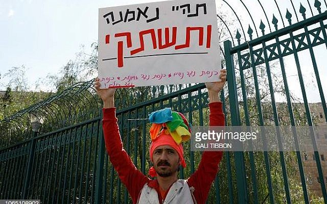 "An Israeli artist holds up a sign during a protest against a new law by culture minister Miri Regev, on November 25, 2018, in front of the Knesset, Israeli parliament in Jerusalem.  The Hebrew sign reads:""be loyal and shut up"" (referring to the parliament ) - The bill conditioning arts funding on 'loyalty' to the state approved for final votes, the artists say the law will essentially enshrine state censorship over the arts. (Photo by GALI TIBBON / AFP)        (Photo credit should read GALI TIBBON/AFP/Getty Images)"