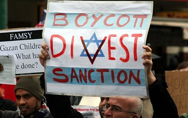 Protestor holds a sign urging the boycott, divestment and sanction of Israel (Jewish News)