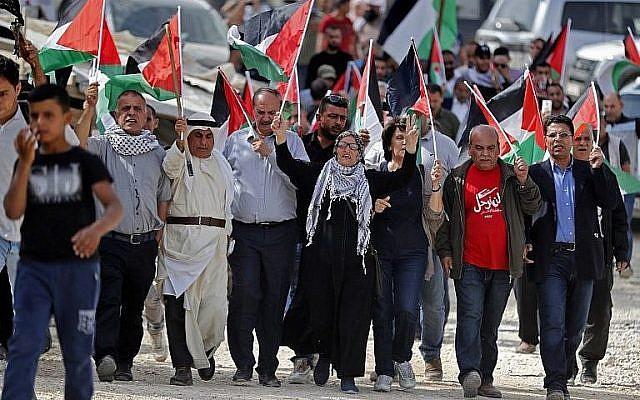 Illustrative. Palestinian wave flags during a demonstration at the West Bank Bedouin village of Khan al-Ahmar over Israel's plans to demolish it, on October 19, 2018. (Ahmad Gharabli/AFP)
