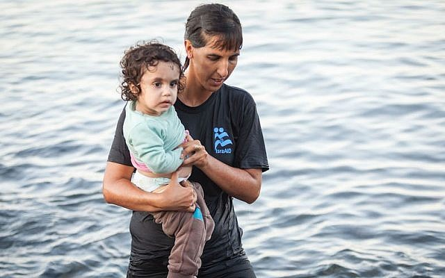 Illustrative. Tali Shaltiel, an Israeli physician, taking a Syrian child from a dinghy that arrived at a beach on the Greek island of Lesbos. (Boaz Arad/IsraAID)