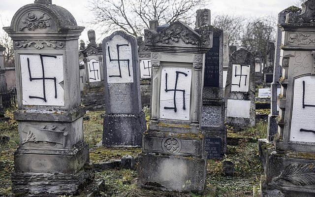 Illustrative. Jewish tombstones are seen desecrated with swastikas in the Herrlisheim Jewish cemetery, north of Strasbourg, eastern France, December 13, 2018. (AP Photo/Jean-Francois Badias)