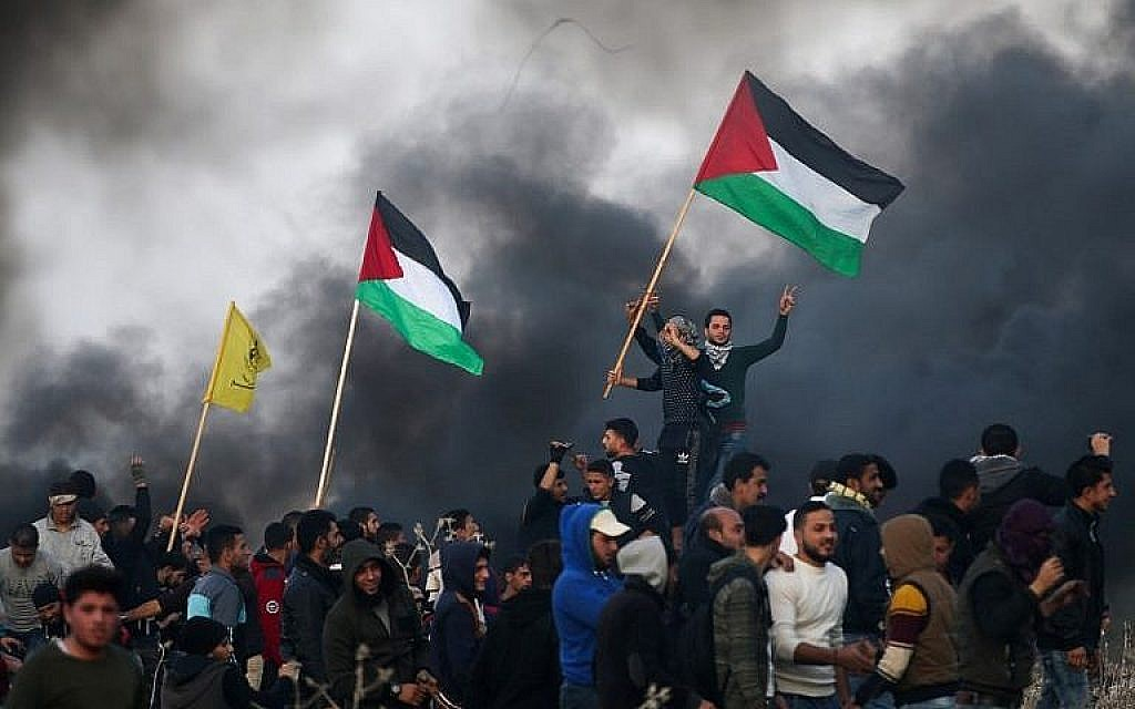 Palestinian protesters wave national flags during clashes with Israeli security forces on the eastern outskirts of Gaza City, near the border with Israel, on January 12, 2018. (AFP Photo/Mohammed Abed)