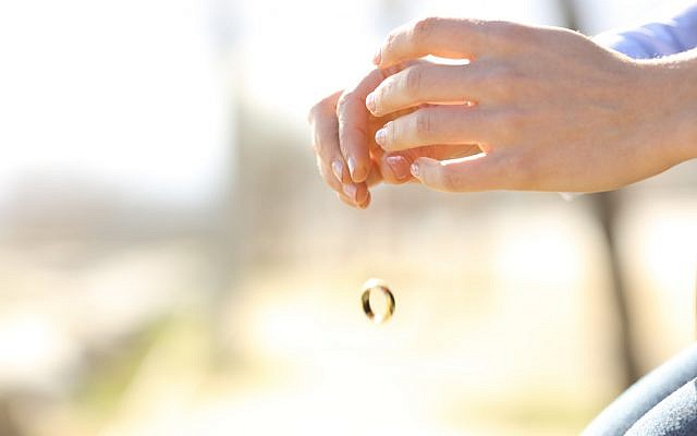 Illustrative. A woman tosses her wedding ring. (iStock)