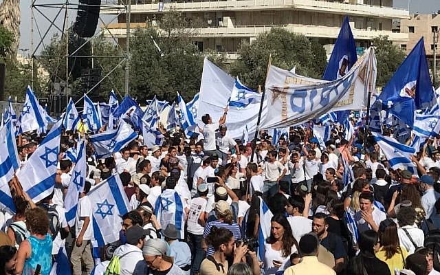 Illustrative. Hundreds of revelers wave Israeli flags as they they prepare to march their way through the city towards the Western Wall for Jerusalem Day. (Like Tress/Times of Israel)
