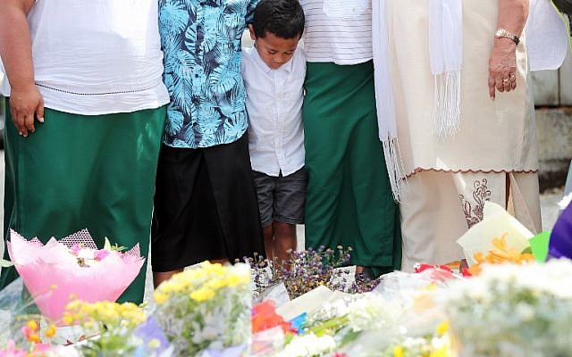 Residents pay their respects by placing flowers for the victims of the mosques attacks in Christchurch at the Masjid Umar mosque in Auckland on March 17, 2019. - The death toll from horrifying shootings at two mosques in New Zealand rose to 50, police said Sunday, as Christchurch residents flocked to memorial sites and churches across the city to lay flowers and mourn the victims. (MICHAEL BRADLEY / AFP)