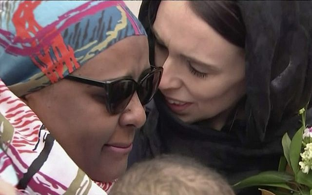 New Zealand's Prime Minister Jacinda Ardern, right, consoles a woman as she visited Kilbirnie Mosque to lay flowers among tributes to Christchurch attack victims, in Wellington, Sunday, March 17, 2019. (from video - TVNZ via AP)