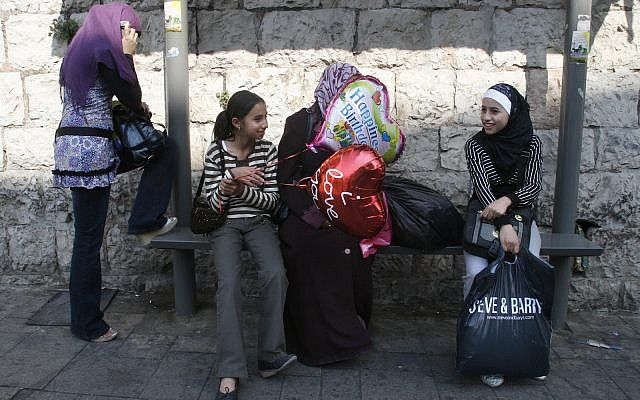 A young girl sits with balloons with other muslim women at a bus stop in East Jerusalem. October 02, 2008. (Lara Savage/Flash90)