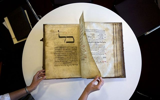 A library official shows a 13th-century German prayer book containing the earliest evidence of the Yiddish language, at Israel's National Library in Jerusalem, October 5, 2014. (AP/Sebastian Scheiner)