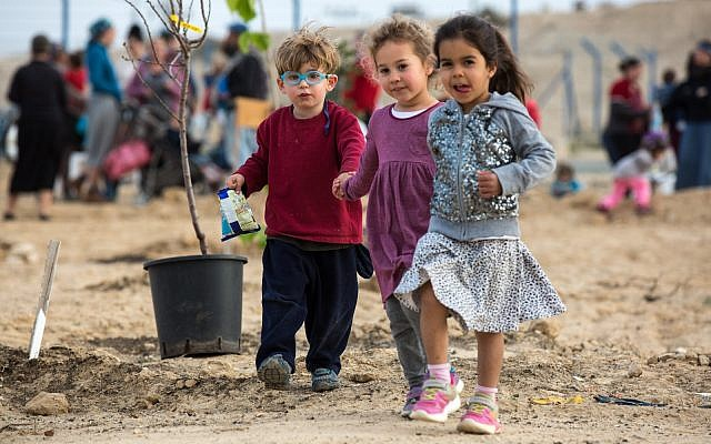 Local children at the first tree planting of the 'White Hill Farm', an urban agricultural center for residents of Yerucham and the neighboring Bedouin community of Rachma. February, 2018. (Courtesy of Atid Bamidbar).