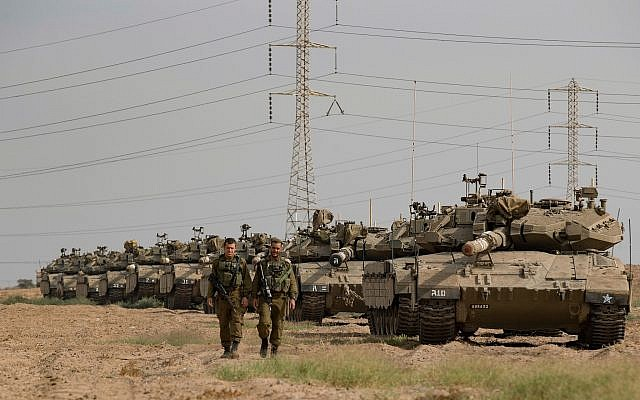 Israeli soldiers seen walking next to Merkava tanks that are stationed in an open area near Israel's border with the Gaza Strip on October 19, 2018. (Photo by: JINIPIX via Jewish News)