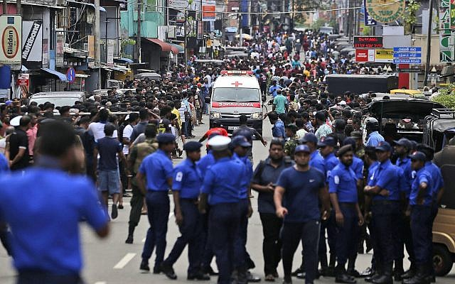 Sri Lankan police officers clear the road as an ambulance drives through carrying injured of Church blasts in Colombo, Sri Lanka, Sunday, April 21, 2019. A Sri Lanka hospital spokesman says several blasts on Easter Sunday have killed dozens of people. (AP Photo/Eranga Jayawardena via Jewish News)