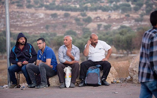 Palestinian men waiting by the side of the road near Checkpoint 300 in Bethlehem, minutes from Jerusalem. (Laura Ben-David)