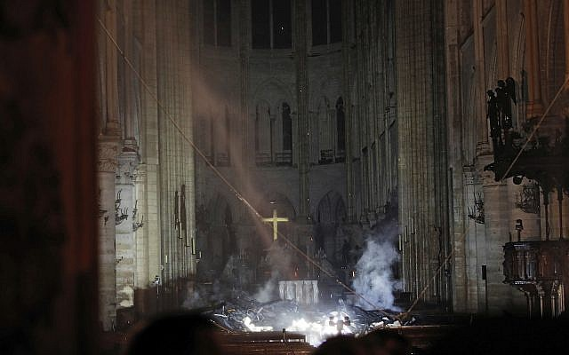 Smoke is seen in the interior of Notre Dame Cathedral in Paris, Monday, April 15, 2019 (Philippe Wojazer/Pool via AP)