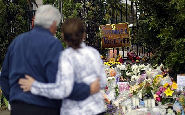 A couple embrace near a growing memorial across the street from the Chabad of Poway synagogue in Poway, Calif., on Monday,, April 29, 2019 (AP Photo/Greg Bull)
