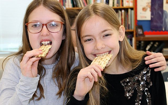 Fifth-grade students Lilah Stein and Nina Olson enjoy the afikoman (photo credit: Ali Reingold)