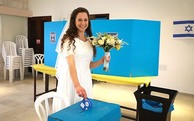 Israeli bride Tsufit Lam casts her ballot at a voting station in Elazar, in Gush Etzion, during the Knesset Elections, on April 9, 2019. (Gershon Elinson/Flash90)