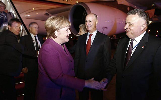 German Chancellor Angela Merkel shakes hands with Israeli Ambassador to Germany Jeremy Issacharoff at Ben Gurion Airport on October 3, 2018, as Minister Tzachi Hanegbi looks on. (Avi Davidi/Foreign Ministry)