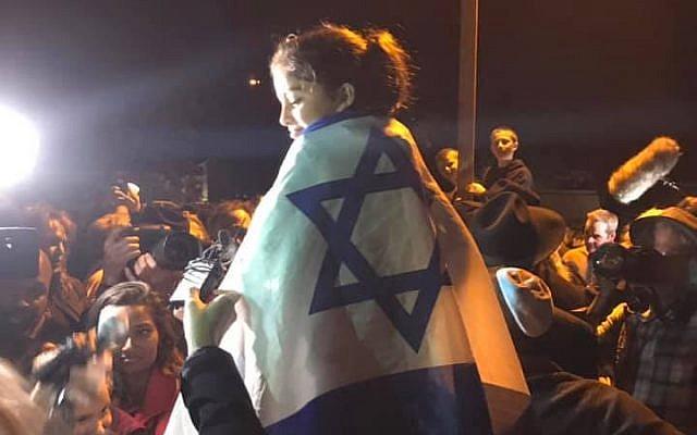 Noya Dahan sits atop her father's shoulders draped in the Israeli flag. Photo- Aaron Raimi