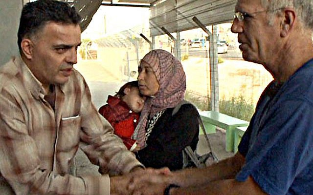 Yuval Roth, founder of Road to Recovery, with Mohammed Kabeh and his family at the border crossing. (Courtesy of Road to Recovery).